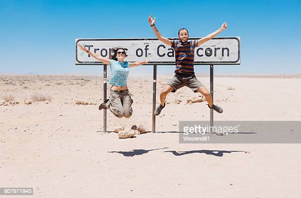 Namibia, Namib desert, Swakopmund, traveler couple jumping next to the sign of the Tropic of Capricorn