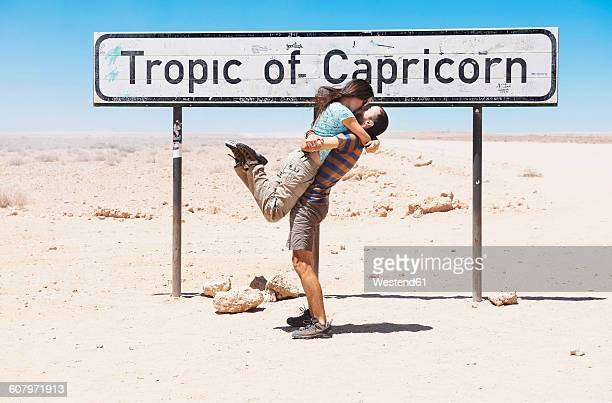 Namibia, Namib desert, Swakopmund, traveler couple kissing next to the sign of the Tropic of Capricorn