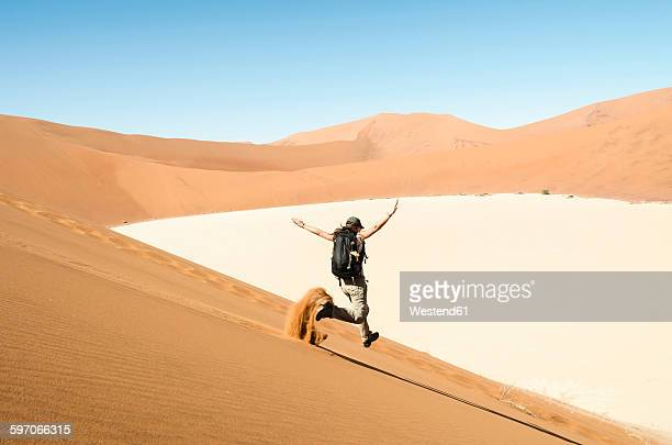 Namibia, Namib Desert, woman running down a dune on the way to Deadvlei