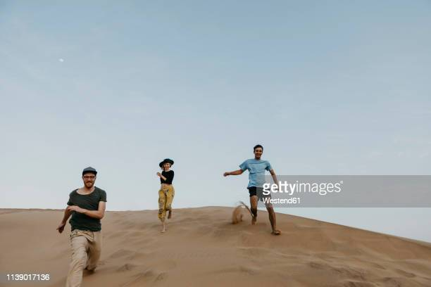 namibia, namib, three friends running down desert dune having fun - extreme terrain stock pictures, royalty-free photos & images