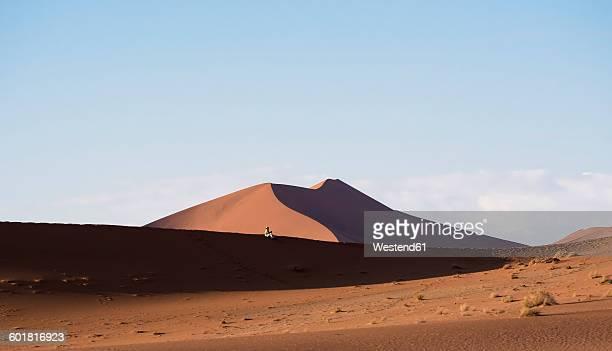 Namibia, Naukluft Park, man sitting on dune of Namib Desert
