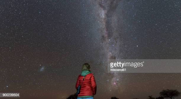 Namibia, Region Khomas, near Uhlenhorst, Astrophoto, Stargazing woman observing the Southern Cross embedded in the Milky Way band