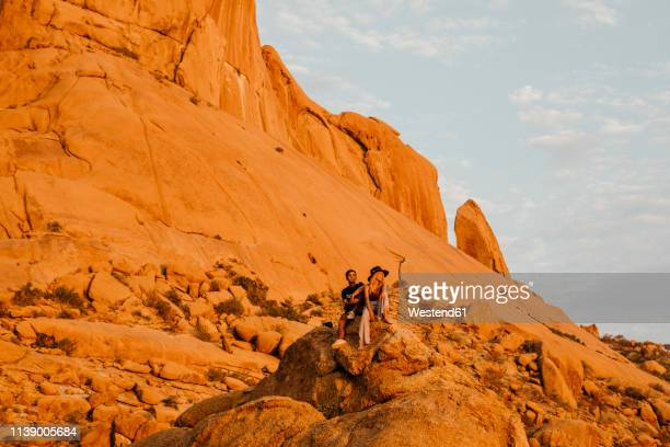namibia, spitzkoppe, couple sitting on a rock at sunset - extreem terrein stockfoto's en -beelden