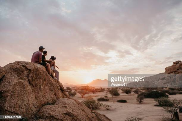 namibia, spitzkoppe, friends sitting on a rock watching the sunset - namibia stock-fotos und bilder