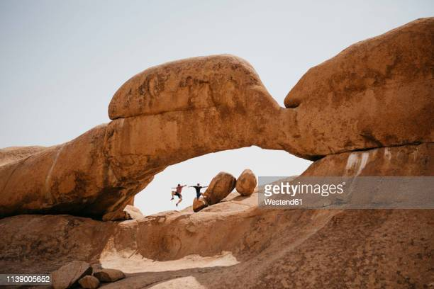 Namibia, Spitzkoppe, two friends jumping at rock formation