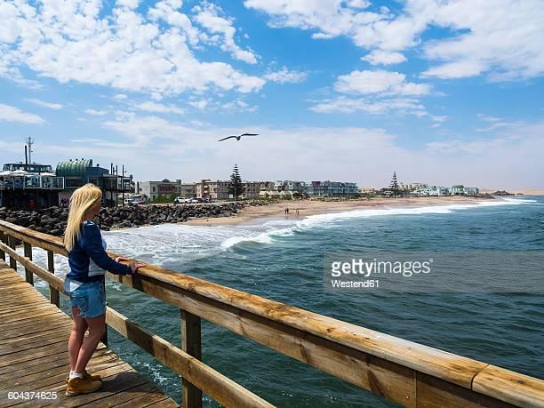 Namibia, Swakopmund, blond woman looking from pier to beach