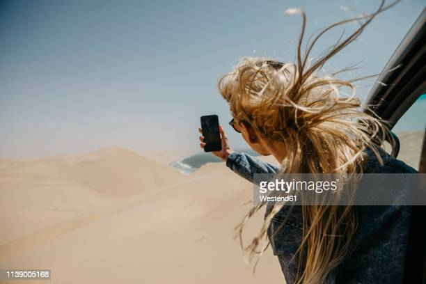 namibia, walvis bay, namib-naukluft national park, sandwich harbour, woman leaning out of car window taking cell phone picture - junge frauen fotos stock-fotos und bilder