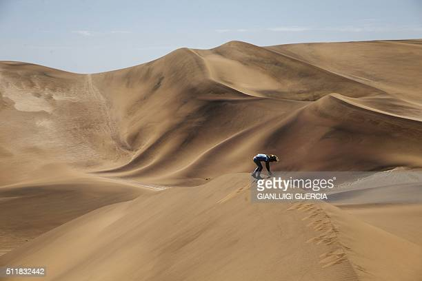 A Namibian child part of a group of tourists on a desert day tour plays on sand dunes in the desert area of the Dorob National Park part of the Namib...