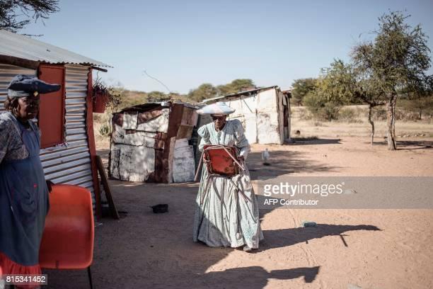 Namibian Herero elderly woman Sarafia Komomungondo 83 and Lidya walk thtough the yard outside their houses on the outskirts of the impoverished town...