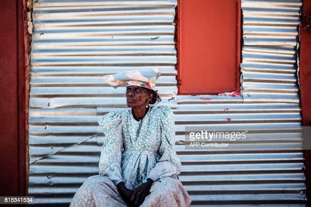 Namibian Herero elderly woman Sarafia Komomungondo sits by a corrugated iron shack on the outskirts of the impoverished town of Okakarara on June 22...