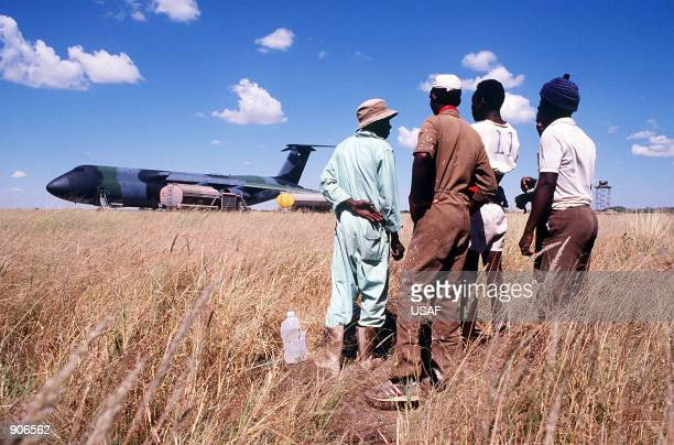 Namibian workers watch operations following the landing of a Military Airlift Command C5B Galaxy aircraft at Grootfontein Logistics Base The Galaxy...