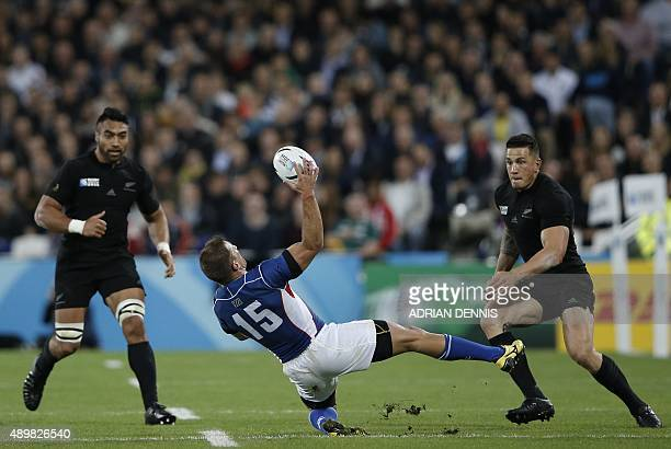 Namibia's fullback Johan Tromp falls with the ball next to New Zealand's centre Sonny Bill Williams and New Zealand's number 8 Victor Vito during a...