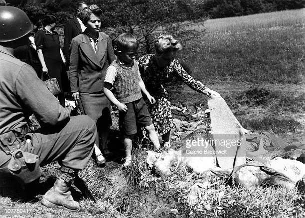 Nammering Victims German civilians are overcome as they walk past the exhumed bodies of some of the 800 slave workers murdered by SS guards near...