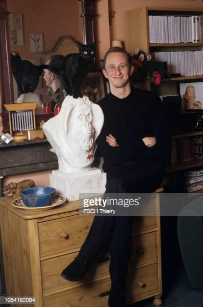 Namur Belgique Décembre 1994 L'acteur Benoît POELVOORDE chez lui avec son chat 'Ecco' Ici les bras croisés assis sur une commode à côté d'une...