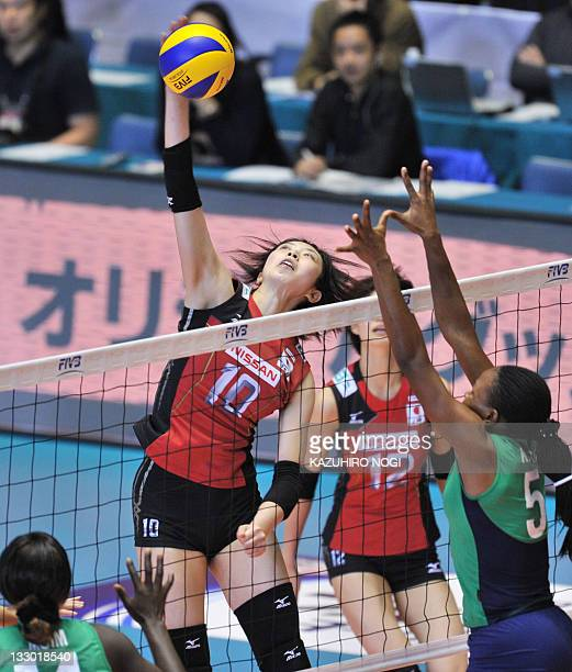 Nana Iwasaka of Japan spikes the ball over Mercy Moim and Diana Khisa of Kenya during their World Cup women's volleyball tournament in Tokyo on...
