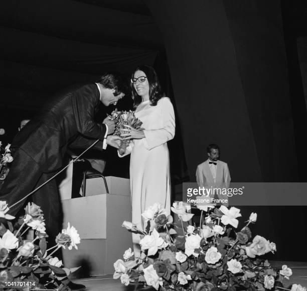 Nana Mouskouri assistant au festival de 'La rose de France de la chanson' est sur la scène avec JeanClaude Brialy en France en juin 1967