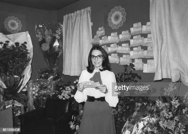 Nana Mouskouri ouvre un télégramme de félicitations lors de la première de son spectacle à l'Olympia le 8 octobre 1971 à Paris France