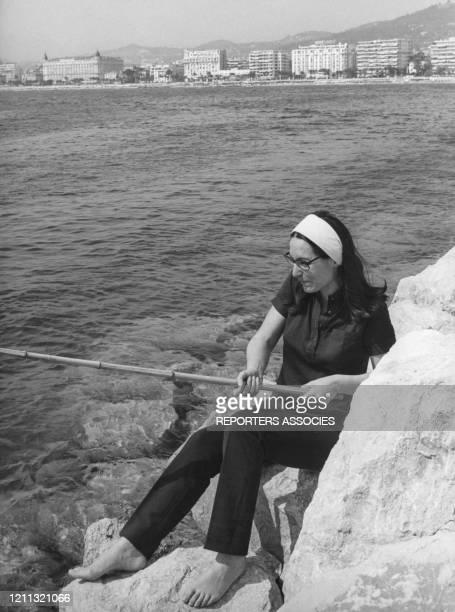 Nana Mouskouri pêche à la ligne à Cannes en France, circa 1960.