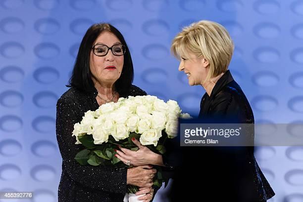 Nana Mouskouri receives flowers from Carmen Nebel at the 'Willkommen bei Carmen Nebel' show at Velodrom on September 13 2014 in Berlin Germany