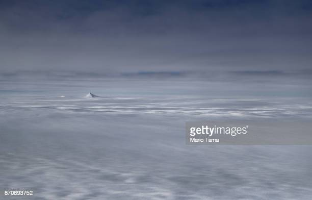 A nanatuk or mountain peak is seen projecting through ice as seen from NASA's Operation IceBridge research aircraft in the Antarctic Peninsula region...