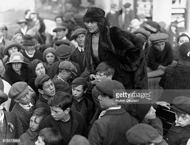Nancy Astor amongst a group of children during the 1923 election campaign in her constituency of Plymouth. She succeeded her husband in the seat in...