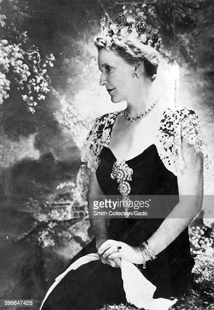 Nancy Astor, first female member of parliament, in a seated portrait, wearing a crown and looking to the side, her hands folded in her lap, 1953.