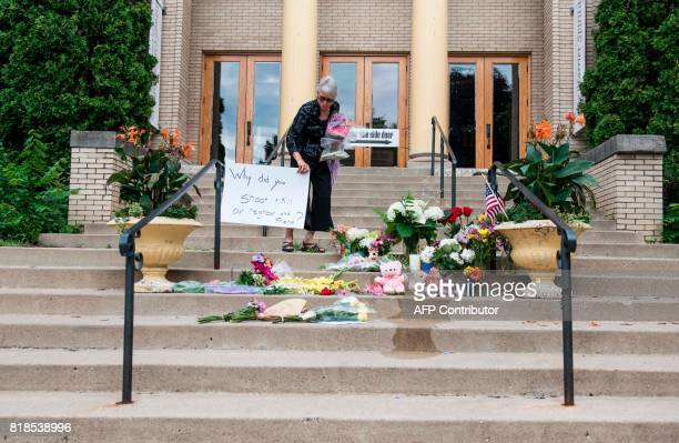 Nancy Coune administrator of the Lake Harriet Spiritual Community centre places flowers and signs memorializing Justine Damond at a makeshift...