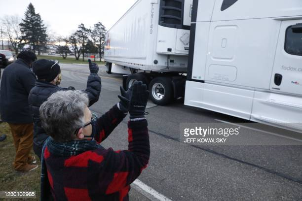 Nancy Galloway and Susan Deur cheer as trucks carrying the first shipment of the Covid-19 vaccine that is being escorted by the US Marshals Service,...