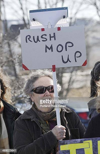 Nancy Greenleaf of Portland holds up a mop with a sign Rush Mop Up during a protest at Portland Radio Group to urge WGAN to drop the Rush Limbaugh...