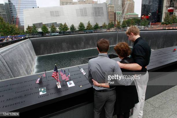Nancy Gregory hugs her sons Carl left and Gregory as they pay their respects to her husband firefighter Ken Kumpel at the National 9/11 Memorial...