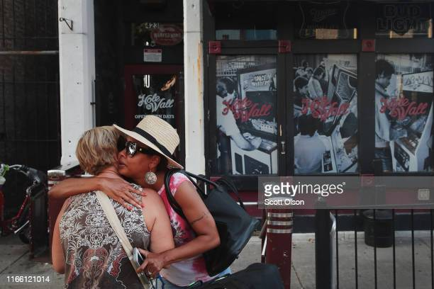 Nancy Hankey and Kim Nelson hug in front of the Hole In The Wall bar in the Oregon District before the start of a memorial service to recognize the...