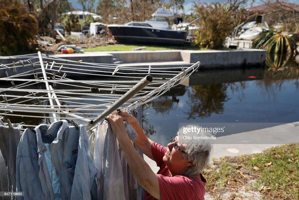Nancy Heater hangs clothes to dry in her yard, September 14, 2017 on Big Pine Key, Florida. Across the canal from Heater, a neighbor's boat is seen that was lifted out of the water by Hurricane Irma's storm surge in the Atlantis Estates neighborhood. Many places in the Keys still lack water, electricity or mobile phone service and residents are still not permitted to go further south than Islamorada. The Federal Emergency Managment Agency has reported that 25-percent of all homes in the Florida Keys were destroyed and 65-percent sustained major damage when they took a direct hit from Hurricane Irma.