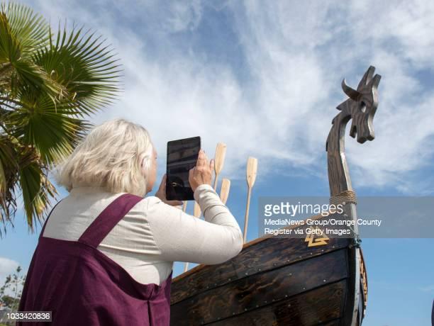 Nancy Kingston of the Vasa Order of America, a Swedish-American organization takes an iPad photo of the Valhalla, a replica knarr Viking ship built...