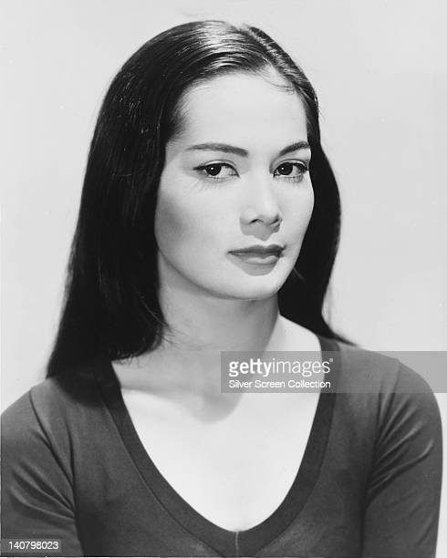 Nancy Kwan US actress wearing a darkneck top in a studio portrait against a white background circa 1960