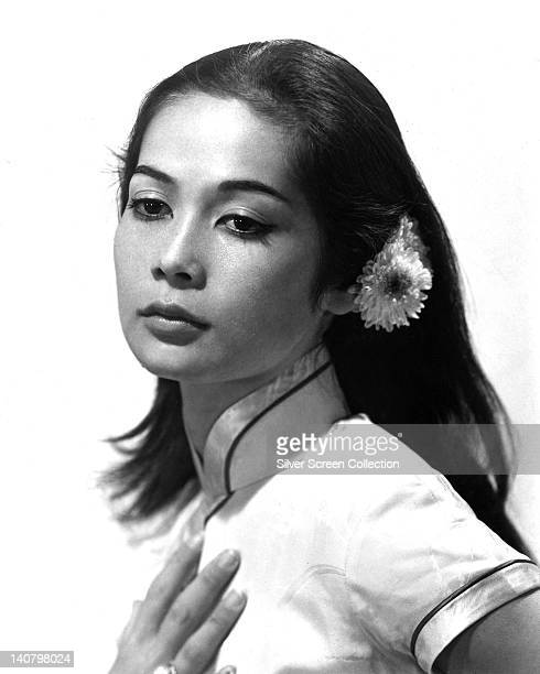 Nancy Kwan US actress wearing a shortsleeve highneck oriental blouse with a flower in her hair in a studio portrait against a white background circa...