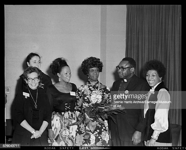Nancy Lee wearing glasses on left with Shirley Chisholm wearing floral dress and holding bouquet standing with three women and minister for...