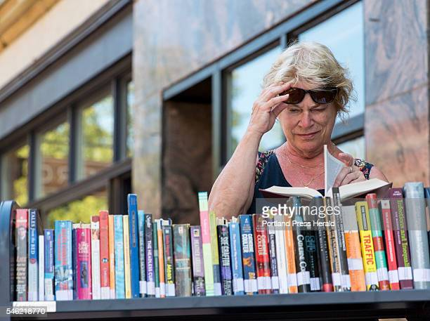 Nancy Leslie of Dover New Hampshire flips through a book outside Longfellow Books in Monument Square