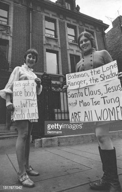 Nancy Moore and Jody Parsons, of the Chicago Women's Liberation Union hold signs as they parade in front of the mansion belonging to Playboy Magazine...