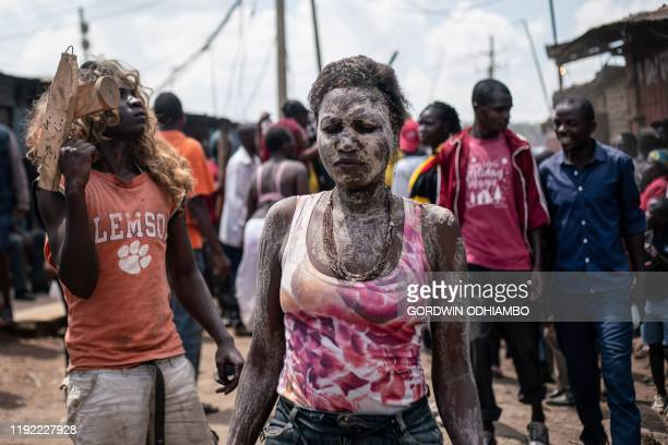 Nancy Nasaka, sister of 18-year-old Isaac Namolo , from Gisu tribe, is smeared by local brew as she waits for her brother's circumsicion at Kibera...