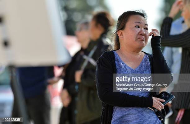Nancy Nguyen dries as she visits a small memorial outside Angel Stadium before a memorial service for the Altobelli family in Anaheim CA on Monday...