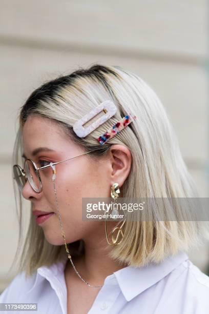 Nancy Pham wearing oversized hair clips round gold frame glasses and oversized pearl and gold abstract earrings is seen during New York Fashion Week...