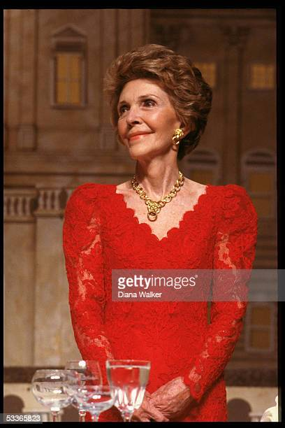 Nancy Reagan decked out in red lace dress gold earrings necklace set at president's dinner