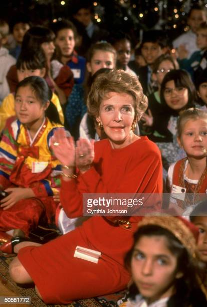 Nancy Reagan enjoying herself seated among boys girls during Christmas Party for diplomatic children