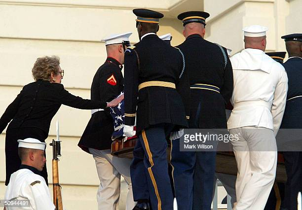 Nancy Reagan reaches out to touch the casket of former President Ronald Reagan as it is carried by an Honor Guard at the US Capitol June 9 2004 in...