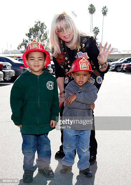 Nancy Sinatra and a firefighter's children pose at Hollywood Chamber Of Commerce's Police And Firefighters Appreciation Day on November 24, 2009 in...