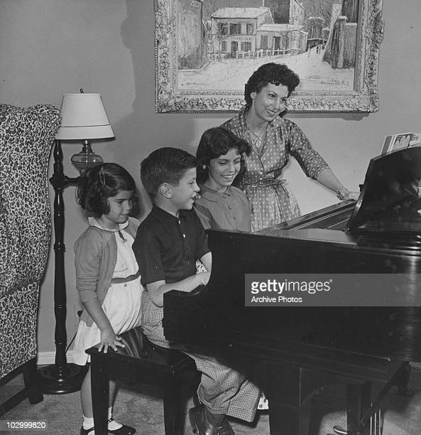Nancy Sinatra Sr sits beside a piano with her young children Nancy Sinatra Frank Sinatra Jr and Tina Sinatra circa 1960's