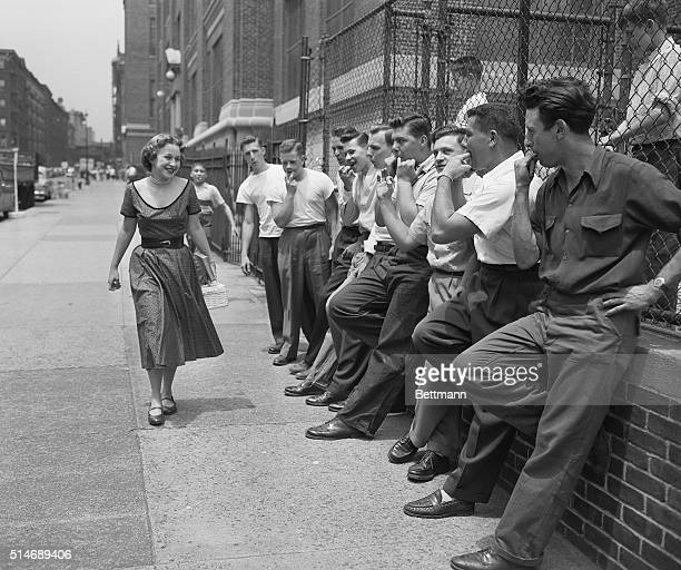 Nancy Ziluck smiles as classmates wolfwhistle at her as she arrives at Julia Richman High School New York