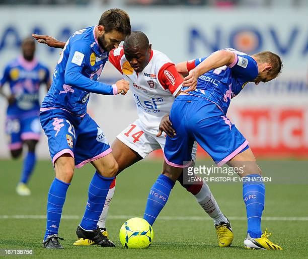 Nancy's Cameroonian forward Paul Alo'o Efoulou fights for the ball with Evian's midfielder Milos Ninkovic and Evian's French midfielder Olivier...