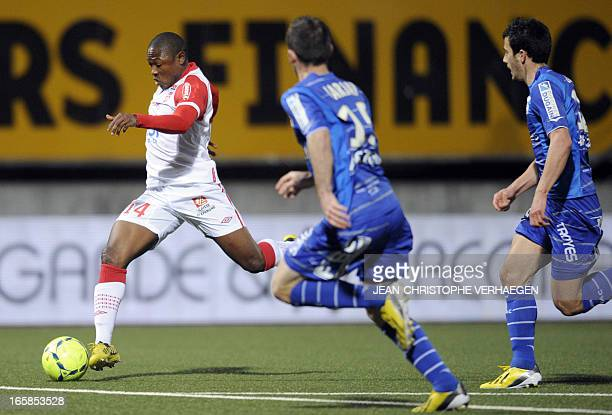 Nancy's Cameroonian forward Paul Alo'o Efoulou vies for the ball with Troyes' French defender Florian Jarjat and French defender Maxime Colin during...