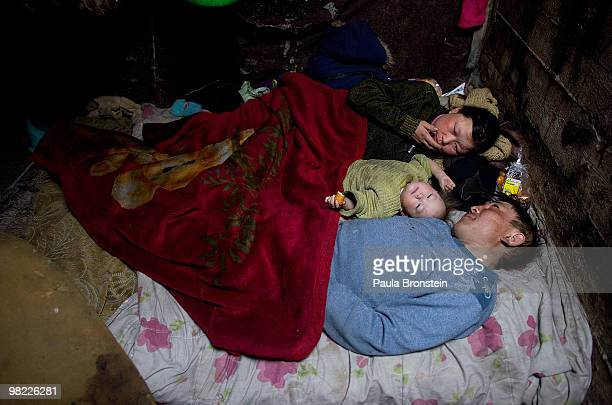Nandintsetseg and Baigalnaa with son Munkhorgil, 18 months, wake up sharing a bed inside the small sewer where the family lives March 15, 2010 in...